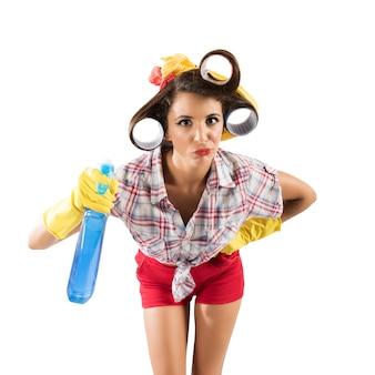 Simpering gospodyni dziewczyna z rękawiczkami i sprayem
