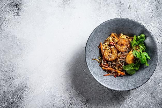 Singapore mei fun. makaron ryżowy z krewetkami, krewetkami, wieprzowiną char siu, marchewką, cebulą, kapustą napa. białe tło. widok z góry. skopiuj miejsce