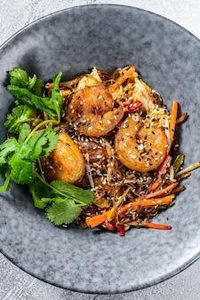 Singapore mei fun. makaron ryżowy z krewetkami, krewetkami, wieprzowiną char siu, marchewką, cebulą, kapustą napa. białe tło. widok z góry