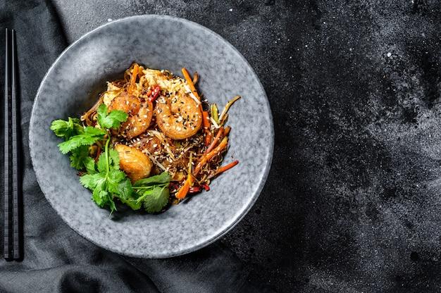 Singapore mei fun. makaron ryżowy z krewetkami, krewetkami, wieprzowiną char siu, marchewką, cebulą, kapustą napa. czarne tło. widok z góry. skopiuj miejsce
