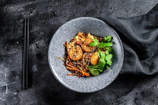Singapore mei fun. makaron ryżowy z krewetkami, krewetkami, wieprzowiną char siu, marchewką, cebulą, kapustą napa. czarne tło. widok z góry