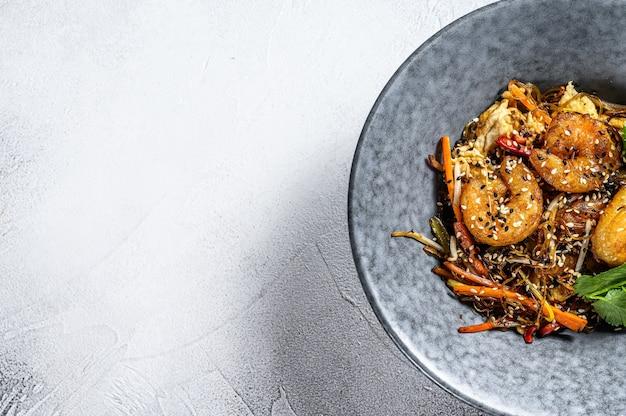 Singapore mei fun. makaron ryżowy z krewetkami, krewetkami, wieprzowiną char siu, marchewką, cebulą, kapustą pekińską. białe tło