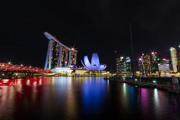 Singapur linia horyzontu pejzaż miejski wokoło mariny zatoki przy nocą.