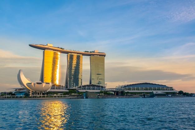 Singapur. marina bay i muzeum artscience. promienie zachodzącego słońca padają na lustrzane okna hotelu marina bay sands