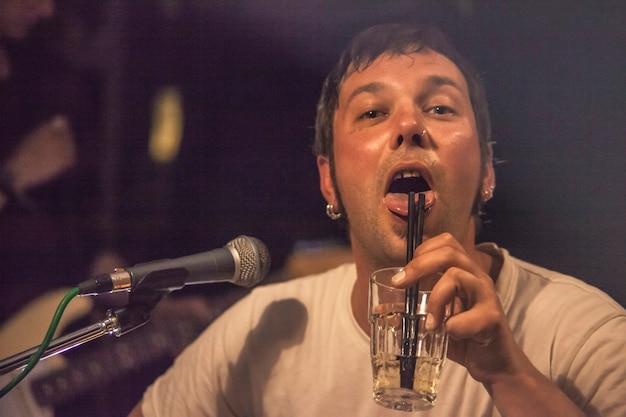 Singer folk śpiewa w pubie przy drinku w szklance