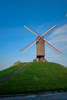 Sint-janshuismolen sint-janshuis mill wiatrak w brugii na zachodzie słońca, belgia