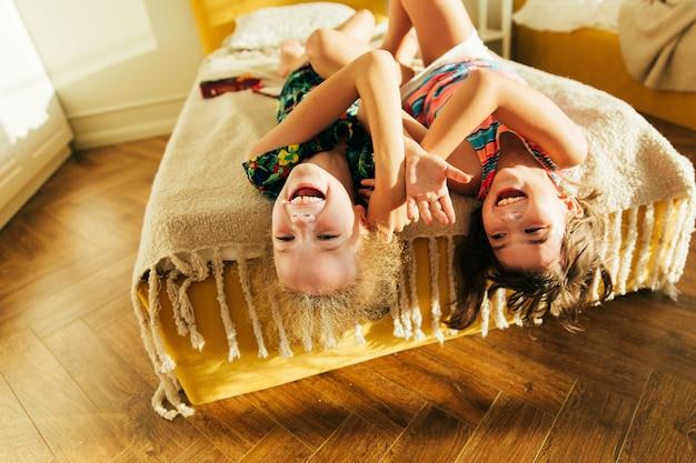 Siostra bawi się w złych i dzieli się chwilami miłości. małe dziewczynki razem zabawy w łóżku. małe dziewczynki bawić się w domu na łóżku.