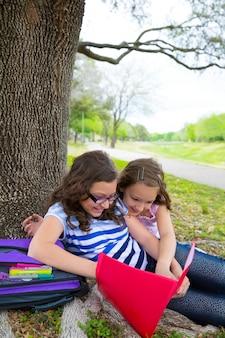 Siostra dziewczyny pończochy zrelaksowany pod drzewem park po szkole