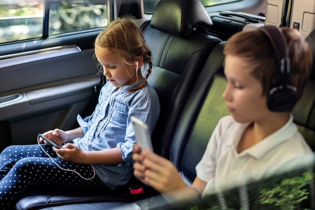 Siostra i brat gra z urządzeniami cyfrowymi w samochodzie