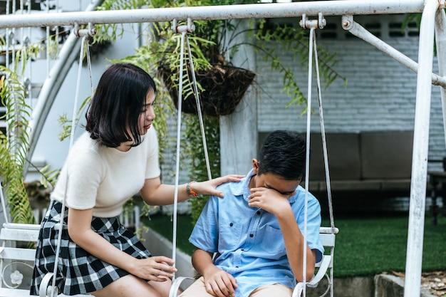 Siostra pocieszyła brata siedzącego płaczącego na huśtawce.