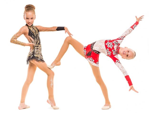 Siostry bliźniaczki dziewczyny w dresach demonstrują ćwiczenie.