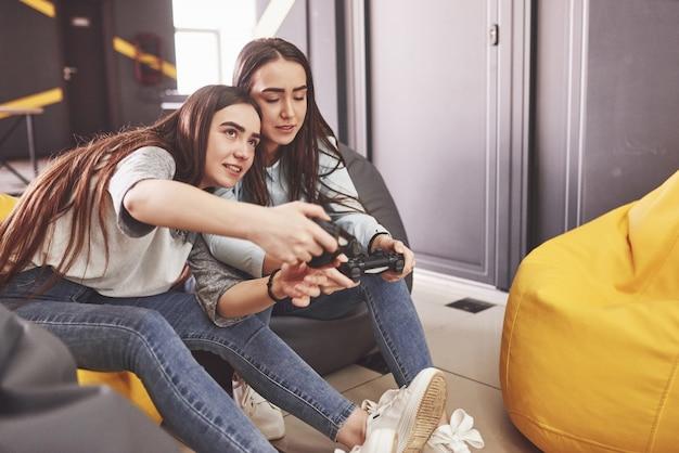 Siostry bliźniaczki grają na konsoli. dziewczyny trzymają joysticki w rękach i dobrze się bawią