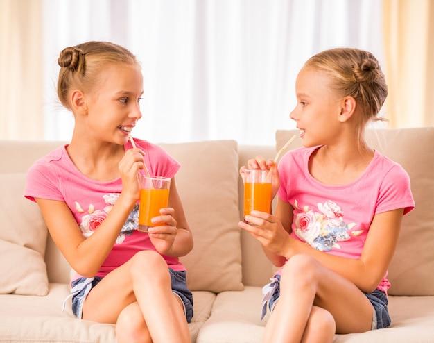 Siostry bliźniaczki piją sok i rozmawiają.
