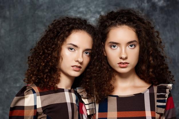 Siostry bliźniaczki pozowanie na szaro