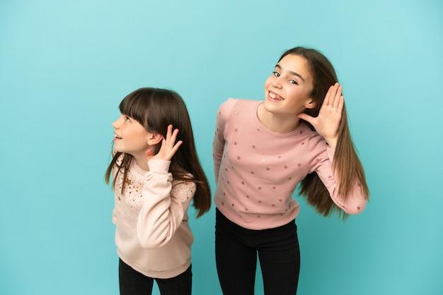 Siostry dziewczynki na białym tle na niebieskim tle, słuchając czegoś, kładąc rękę na uchu