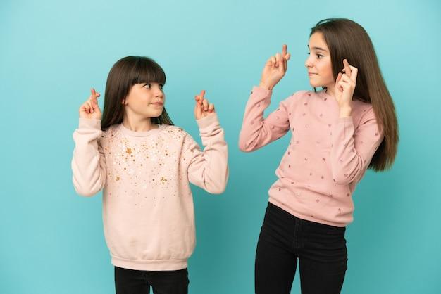 Siostry dziewczynki na białym tle na niebieskim tle z palcami skrzyżowanymi i życząc wszystkiego najlepszego
