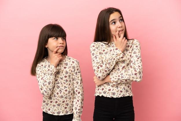 Siostry dziewczynki na białym tle na różowym tle, mając wątpliwości, patrząc w górę