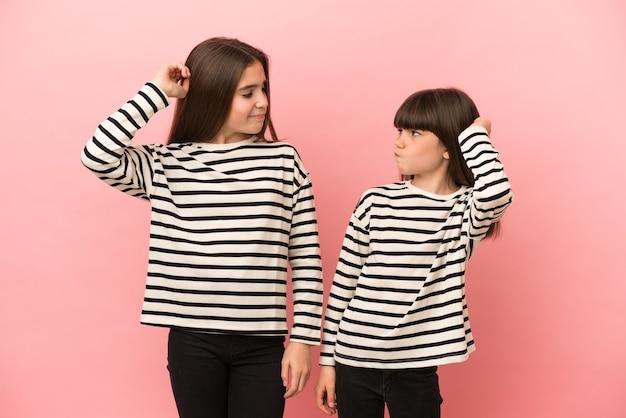 Siostry dziewczynki na białym tle na różowym tle, mając wątpliwości podczas drapania głowy