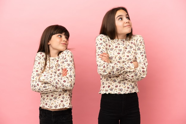 Siostry dziewczynki na białym tle na różowym tle, robiąc gest wątpliwości podczas podnoszenia ramion