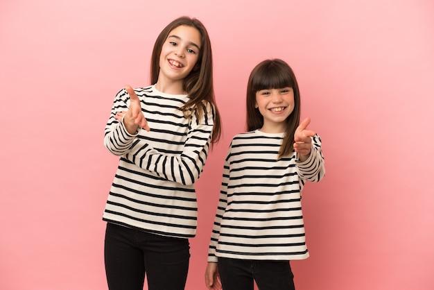 Siostry dziewczynki na białym tle na różowym tle, ściskając ręce za zamknięcie dużo