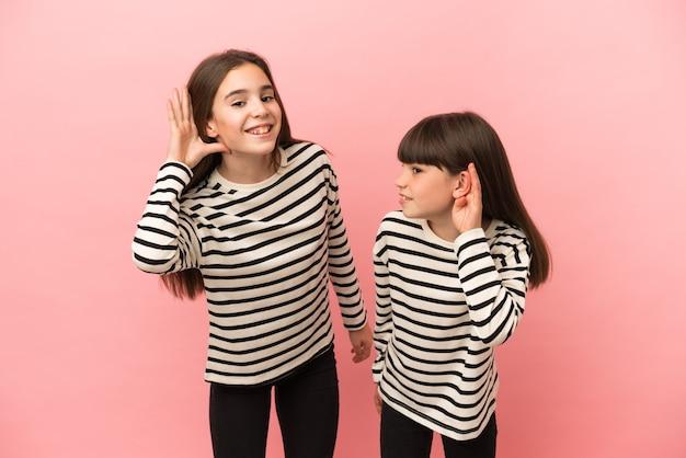 Siostry dziewczynki na białym tle na różowym tle, słuchając czegoś, kładąc rękę na uchu