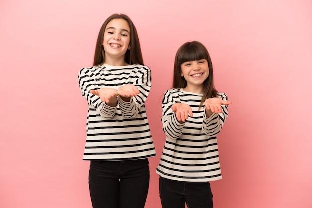 Siostry dziewczynki na białym tle na różowym tle trzymając copyspace wyimaginowane na dłoni, aby wstawić reklamę