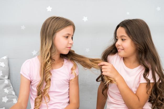Siostry dziewczyny spędzają miło czas komunikując się w sypialni. korzyści z posiadania siostry. niesamowite korzyści z posiadania siostry. siostry starsze lub młodsze są głównym czynnikiem wpływającym na bardziej pozytywne emocje rodzeństwa.