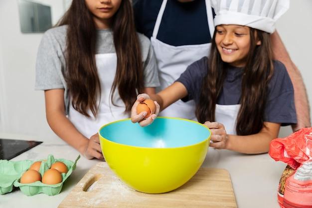 Siostry gotujące w kuchni z ojcem