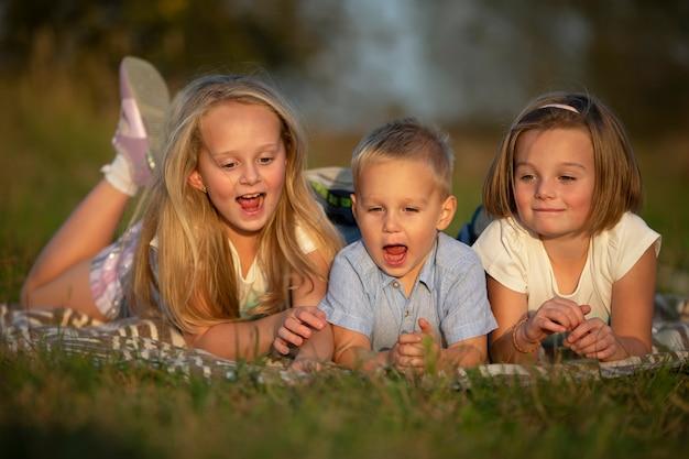 Siostry i braciszek leżą na trawie. dzieci bawią się na łące. szczęśliwa rodzina.
