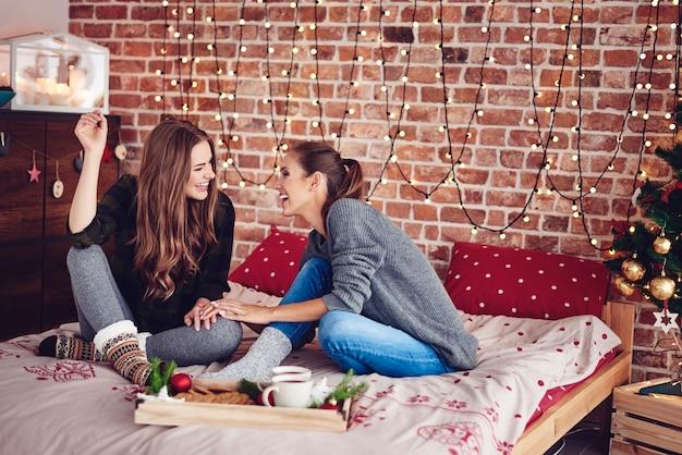 Siostry plotkują i śmieją się w sypialni