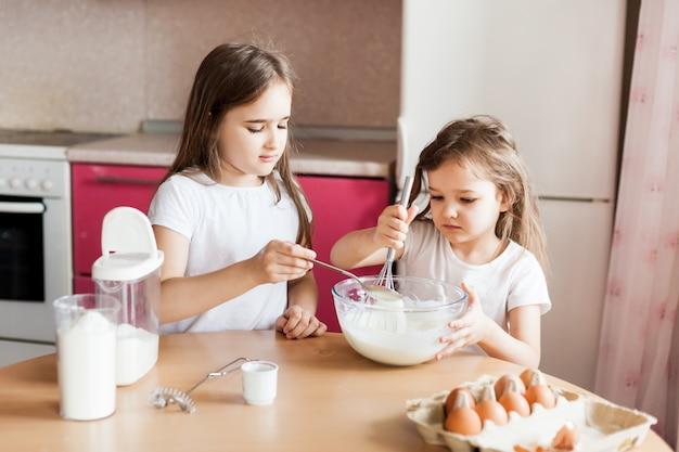 Siostry przygotowują śniadanie, wypieki, mieszają mąkę, mleko, jajka, naleśniki w misce, dzieci pomagają matce, śniadanie rodzinne, gotowanie