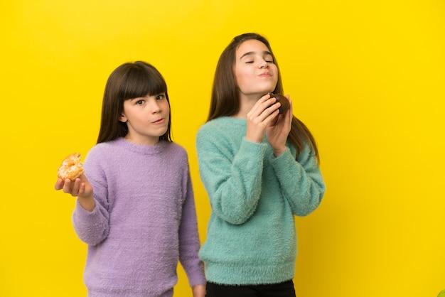 Siostry trzymając pączka na białym tle