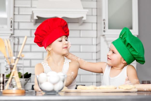 Siostry w jasnych kapeluszach kucharskich pieczą razem w kuchni