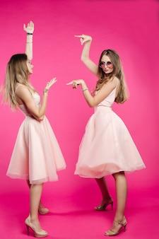 Siostry w różowych sukienkach emocjonalnie pozują i wskazują ręką.