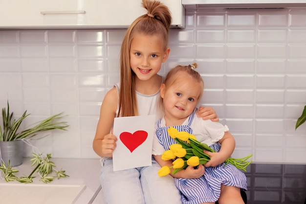 Siostry z bukietem kwiatów i pocztówką w kuchni. dzień ojca.