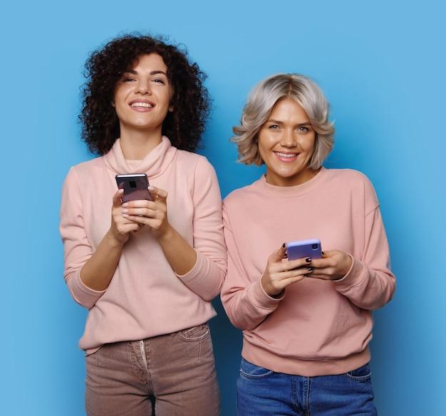 Siostry z kręconymi włosami rozmawiają przez telefon i uśmiechają się