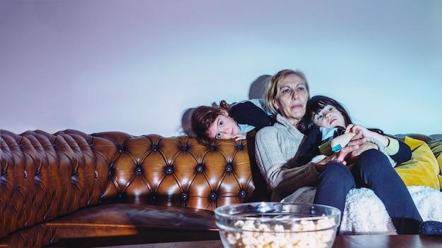 Siostry z matką oglądającą telewizję