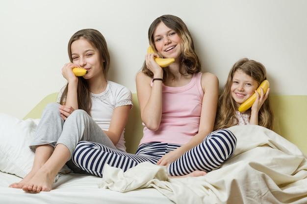 Siostrzane dzieci kep banany jak telefony rozmawiające i śmiejące się