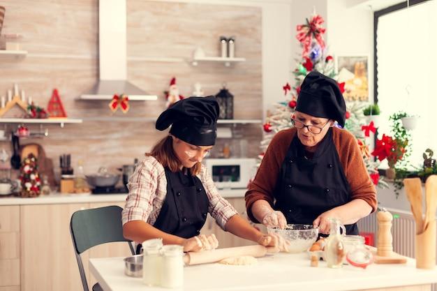 Siostrzenica i babcia w fartuchu w boże narodzenie ugniatają ciasto