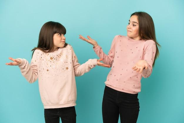 Siostrzyczki dziewczynki na białym tle na niebieskim tle, wykonując nieistotny gest podczas podnoszenia ramion