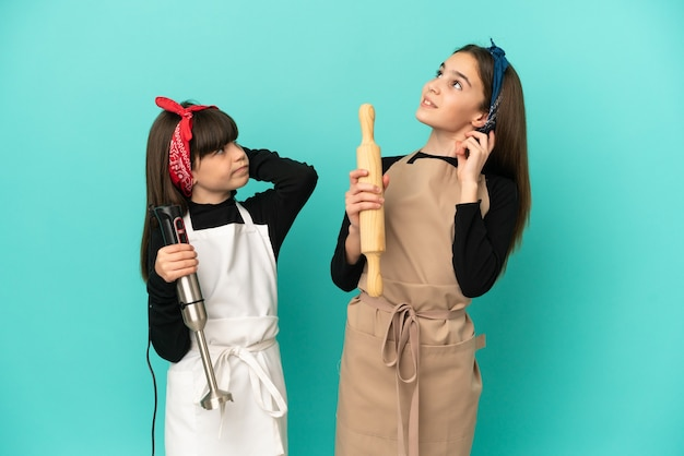 Siostrzyczki gotowanie w domu na białym tle na niebieskim tle myśli pomysł podczas drapania głowy
