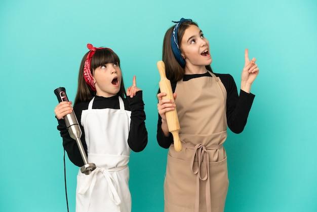 Siostrzyczki gotowanie w domu na białym tle na niebieskim tle myśli pomysł wskazując palcem w górę
