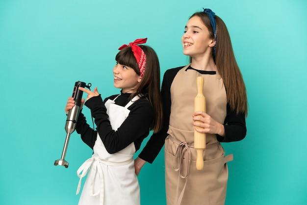 Siostrzyczki gotowanie w domu na białym tle na niebieskim tle przedstawiające pomysł, patrząc w kierunku uśmiechniętym