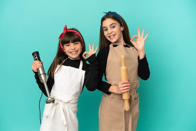 Siostrzyczki gotowanie w domu na białym tle na niebieskim tle przedstawiający znak ok palcami
