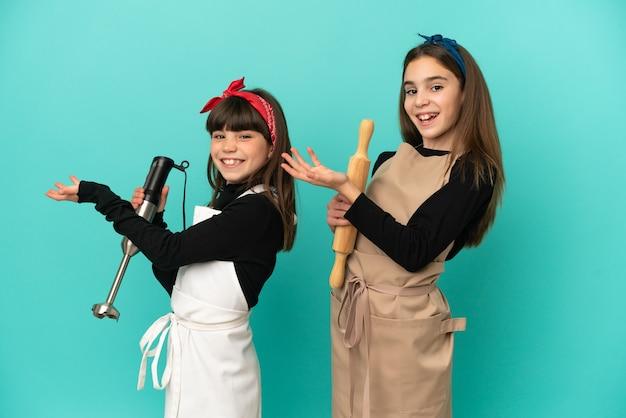 Siostrzyczki gotują w domu na białym tle na niebieskim tle, wyciągając ręce do boku za zaproszenie do przyjścia