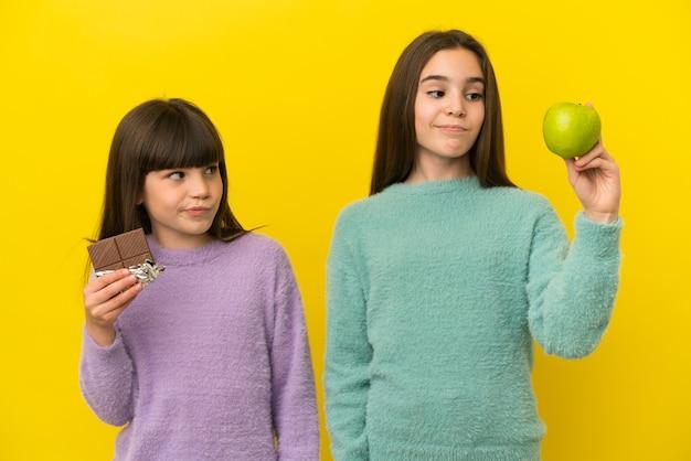 Siostrzyczki na białym tle na żółtym tle mają wątpliwości, biorąc w jednej ręce czekoladową tabletkę i jabłko w drugiej