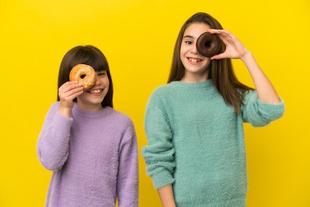 Siostrzyczki na białym tle na żółtym tle trzymając pączka i szczęśliwy