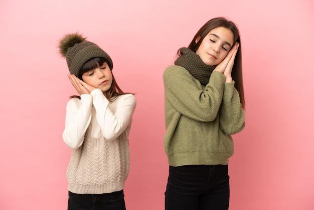 Siostrzyczki na sobie zimowe ubrania na białym tle na różowym tle, wykonując gest snu w dorable wypowiedzi