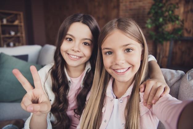 Siostrzyczki pozują razem na kanapie