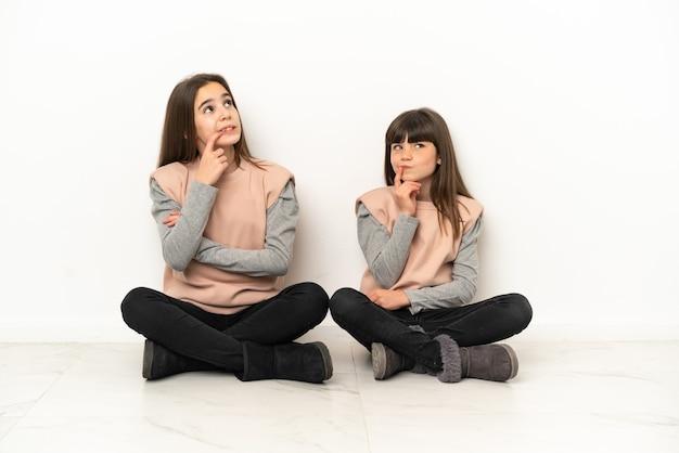 Siostrzyczki siedzi na podłodze na białym tle na białym tle, mając wątpliwości, patrząc w górę